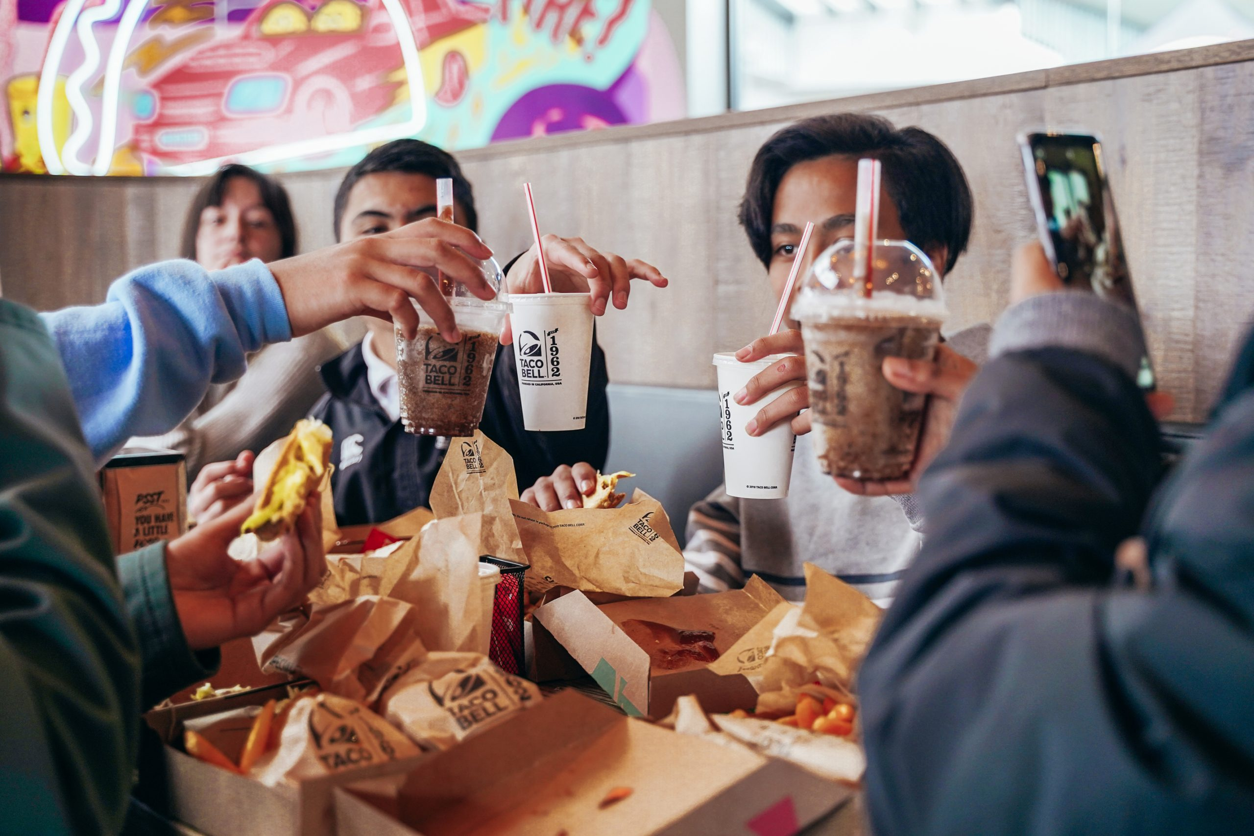 Friends enjoying Taco Bell food and drinks