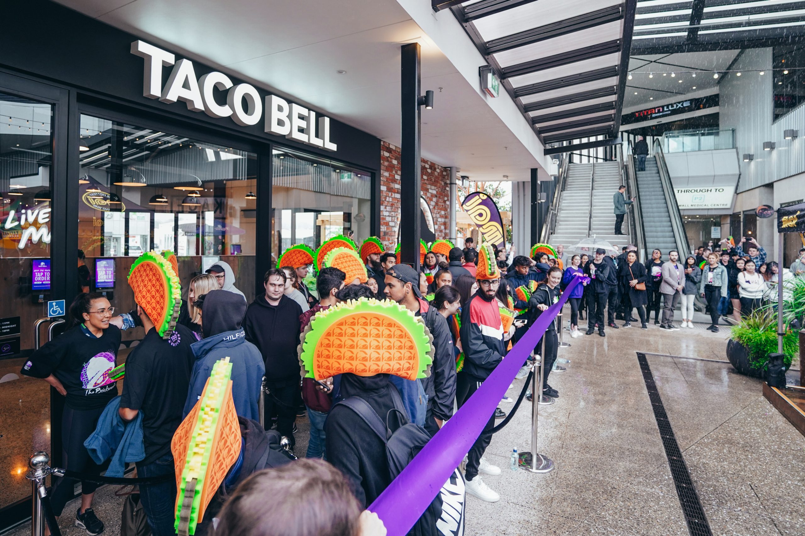 Customers lining up outside Taco Bell wearing brand merchandise