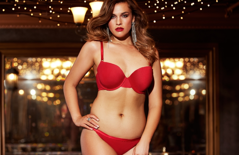 Model in red lingerie standing in front of fairy lights